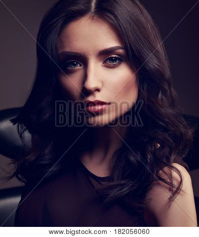 Young Cute Makeup Model In Brown Dress And Curly Hairstyle Posing On Dark Deep Shadow Background. To