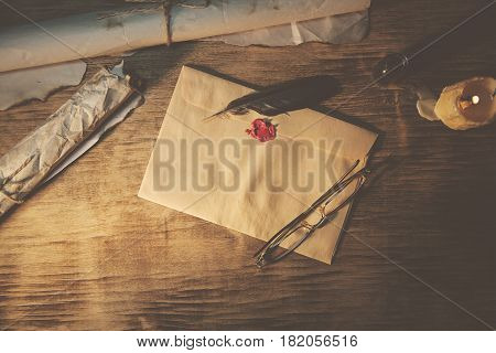 Old feather envelope sealing wax on wooden table
