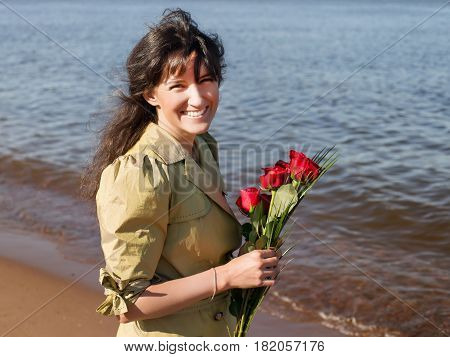 Happy smiling woman in green coat with roses bouquet squinting at direct sun. Outdoor portrait against sea coast