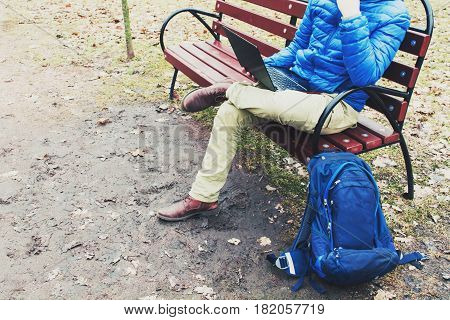 Young man traveler sitting in jacket on bench and looking at laptop in park in spring or autumn