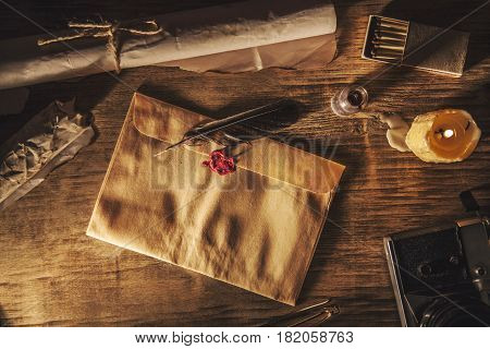 Old feather envelopz and sealing wax on wooden table