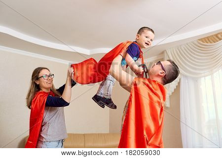A family dressed in superhero costumes plays  the room.
