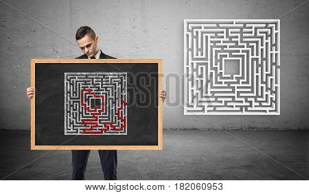 A businessman holding a chalkboard with a picture of a solved maze, unseeing a new maze behind him. Puzzles and problems. Questions and answers. Business advice.