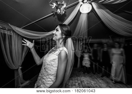 Stylish Happy Bride Throwing Bouquet And Having Fun At The Wedding Reception