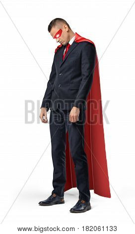 A sad businessman in a superhero red cape standing with his shoulders slumped and looking down. Profit and loss. Unexpected problems. Business pitfalls.
