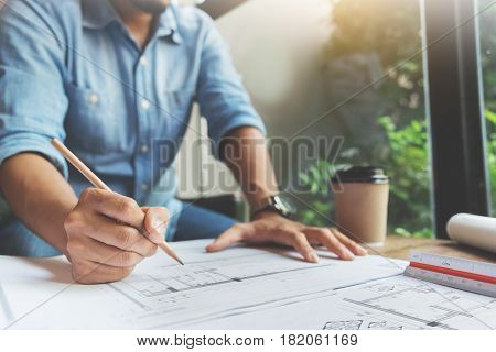 Close Up man hand writing on document papers with pencil. Freelance designer drawing his job.
