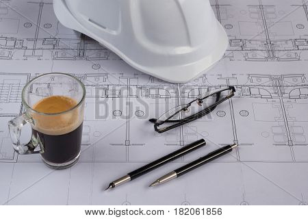 Burgas, Bulgaria - April 9, 2017: Architects workplace - architectural blueprints with safety helmet, glasses, coffee and propelling pencil on table. Top view