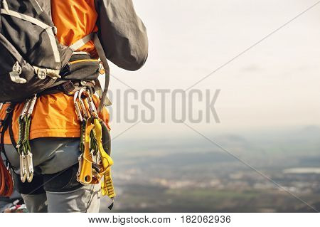 Close-up of a thigh climber with equipment on a belt, stands on a rock on hills background