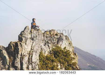 The young climber meditates to nirvana in the lotus position on top of a steep cliff against the backdrop of the city and mountains