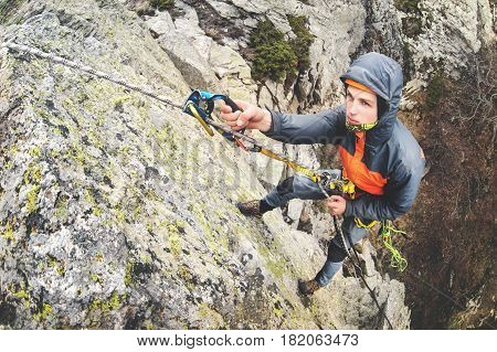 Young white man climbing a steep wall in the mountains, climbing extreme sports, wide angle Horizontal orientation on fisheye