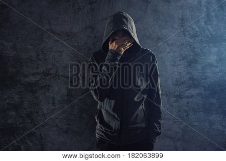 Depressed hooded young adult male person leaning on grungy wall and crying alone in the dark