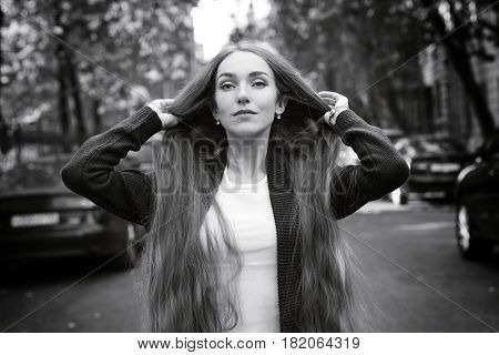 Fashion girl with very long hair against city street. Black and white photo