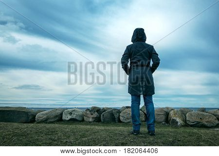 Lonely hooded female person from behind standing at seashore and looking into distance on a cold winter day concept of waiting anticipation hope and expectancy