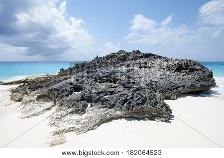 The rock on a beach of uninhabited island Half Moon Cay (Bahamas).