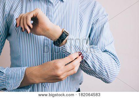 Close-up Of A Woman Buttoning A Shirt