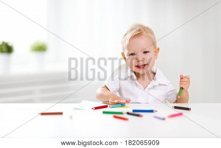 Happy baby boy draws with colored pencils and laughs