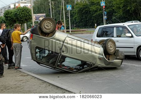 Tyumen, Russia - July 23, 2010: Car crash accident on street, car turned upside-down after road collision