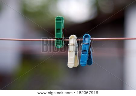 Closeup of Colorful clothes peg on a rope isolated on light blurred background