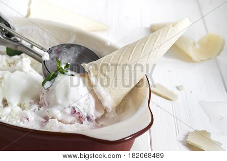 Vanilla ice cream with berry jam and waffle horn