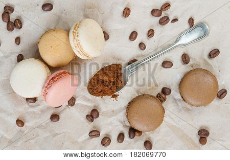 Multicoloured macaroons coffee beans and ground coffee in teaspoon on the background of wrapping paper; top view flat lay