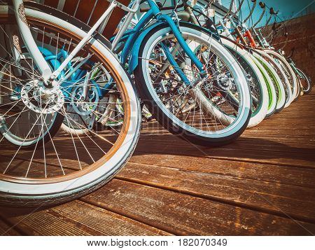 Many bikes in a row on the street. Bicycle parking. Colored bicycles on the street Background