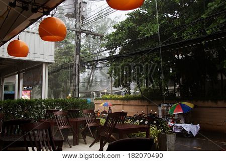 Tropical monsoon rain in Asia. Street restaurant.