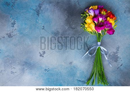 Posy of fresh freesia flowers on gray background with copy space