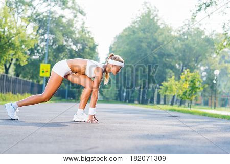 Young woman runner outdoor standing in start pose