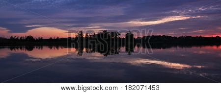 Moody sky reflecting in lake Pfaffikon. Sunset scene in Zurich Canton Switzerland.