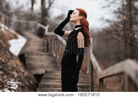 Striking fashionable girl with long red hair in black clothes. Fashionable woman in black dress and long black gloves posing on a background of winter autumn nature. Female street fashionable style. Beautiful elegant fashionable model