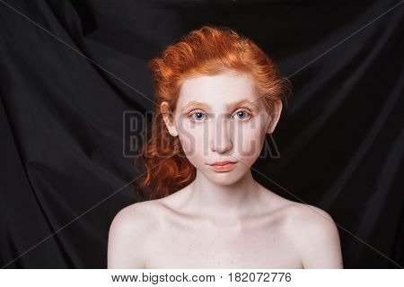 Woman with long curly red hair gathered in ponytail on black background. Red-haired girl with pale skin blue eyes unusual appearance without makeup. Natural beauty. Girl from the era of renaissance. Beautiful clavicles. Two clavicles