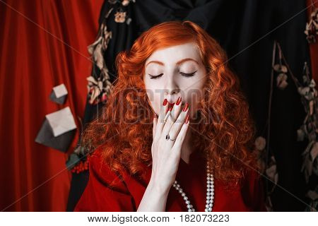 woman smoke with red hair in a red fitting dress with a cigarette smoke in her mouth. Red-haired girl with pale skin and blue eyes with a bright unusual appearance with beads around her neck smoke cigar. Noir image with smoke. Model smoke. Cigarette smo