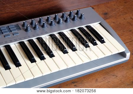 Electronic synthesizer keyboard with many control knobs in silver plastic body on wooden background side view closeup