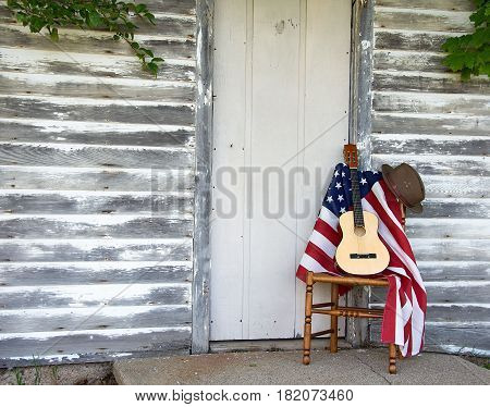 guitar and American flag with brown hat on wooden chair by old door