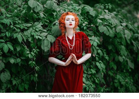 Fashionable woman with red hair and red slinky fashionable dress posing on a background of green leaves. Red-haired fashionable girl with pale skin and blue eyes with a bright unusual appearance with necklace of beads around her neck