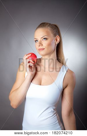 portrait of young sport girl with apple on gray background