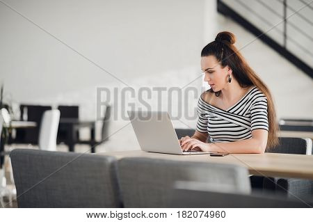 Young female entrepreneur reading electronic book on laptop during lunch in modern restaurant interior. Elegant businesswoman chatting on tablet while sitting in comfortable coffee shop
