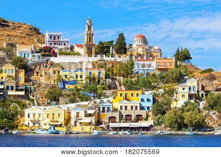 Perfect sunny day and beautiful view from the sea on colorful houses on rocks on Greek island Simi