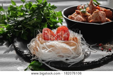 cellophane noodles with half of the tomato, onion and parsley on the Board of black slate with a frying pan filled with fried salmon