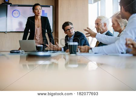 Team of business people sitting together in discussion around conference table. Diverse business group having a meeting in boardroom.