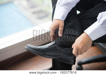 Groom wearing shoes on wedding day, tying the laces and preparing. Business man dressing up with elegant shoes.