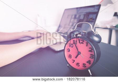 Student is working on project with alarm clock for deadline