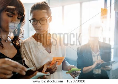Business women discussing in front of glass wall using post it notes and stickers. Corporate professionals using adhesive notes for brainstorming in modern office.