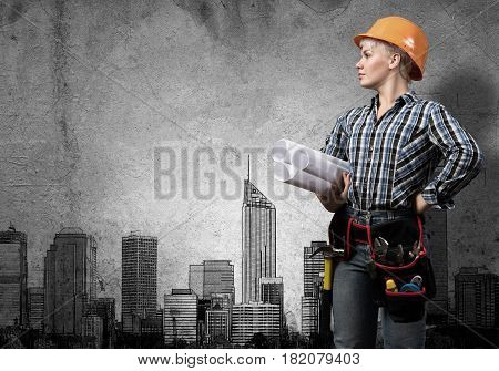 Engineer woman with blueprints and sketches of construction project on wall