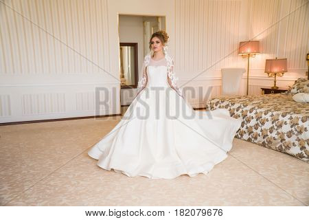 Portrait of beautiful young bride. A girl is posing in a hotel room. A lady Is worth with by the window. bride waiting in hotel