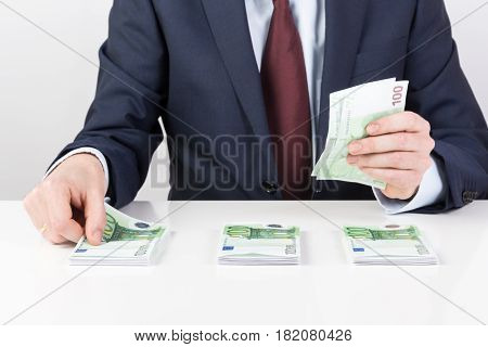 bank teller's hands counting euro banknotes on the table. Financial concept. Closeup.