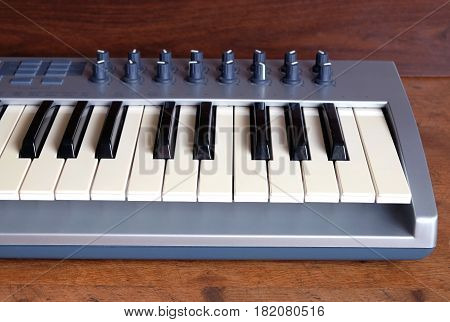 Electronic synthesizer keyboard with many control knobs in silver plastic body on wooden background front view closeup