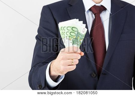 Businessman's hand holding money euro banknotes. Financials investment success and profitable business concept.