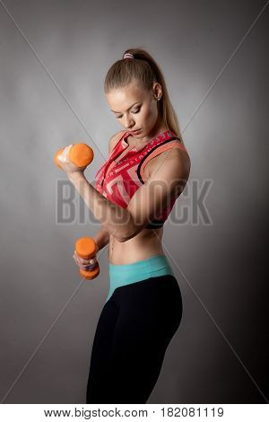 portrait of young sport girl with dumbbells on gray background
