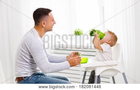 father feeds the baby from the spoon